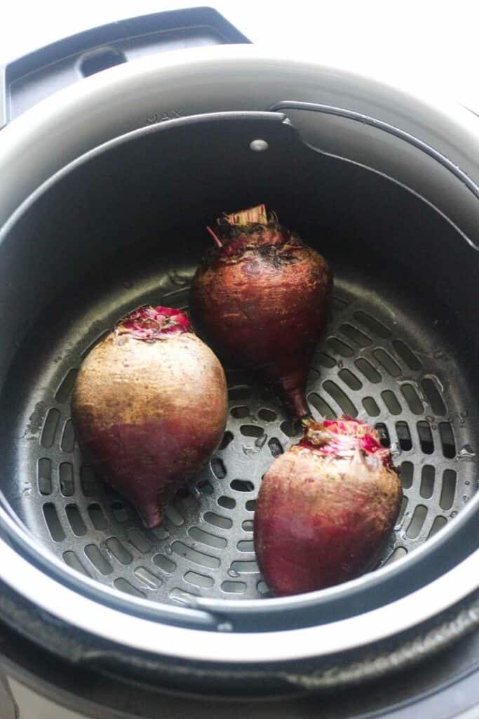 raw skin on beet in the air fryer basket of ninja foodi