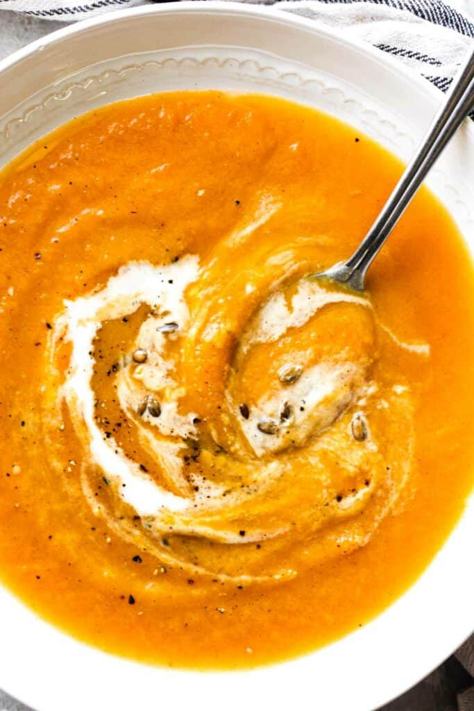 ninja foodi butternut squash soup in a white bowl with spoon in it