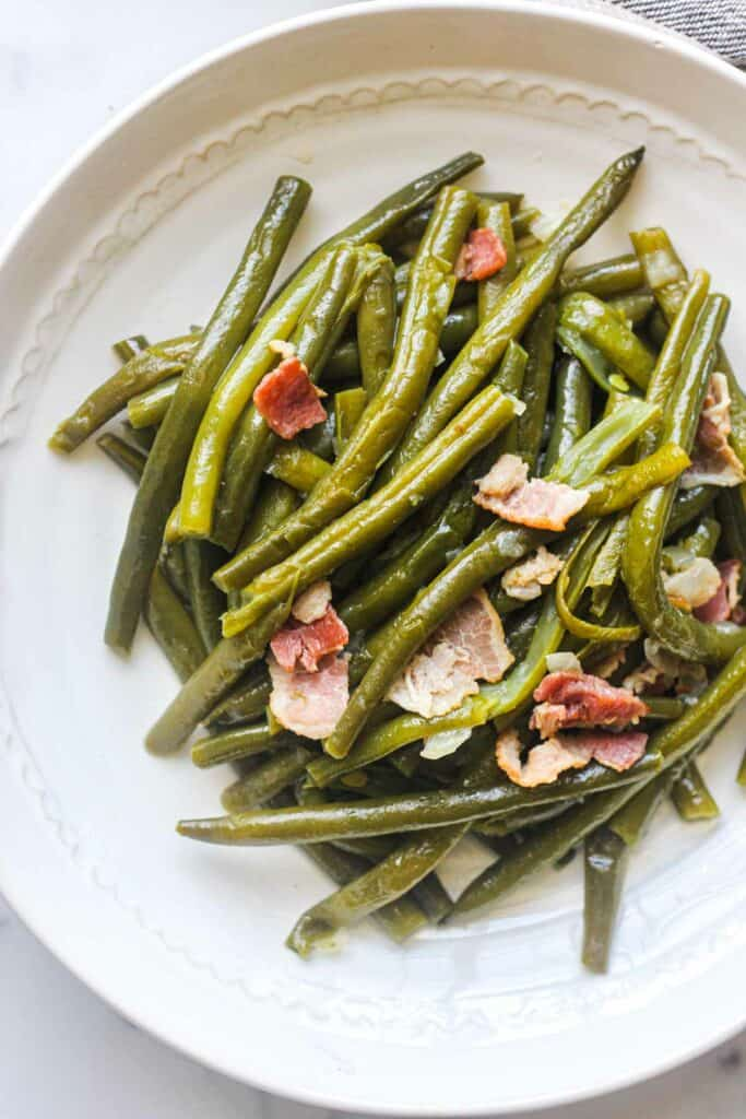 cooked green beans with bacon on the white plate