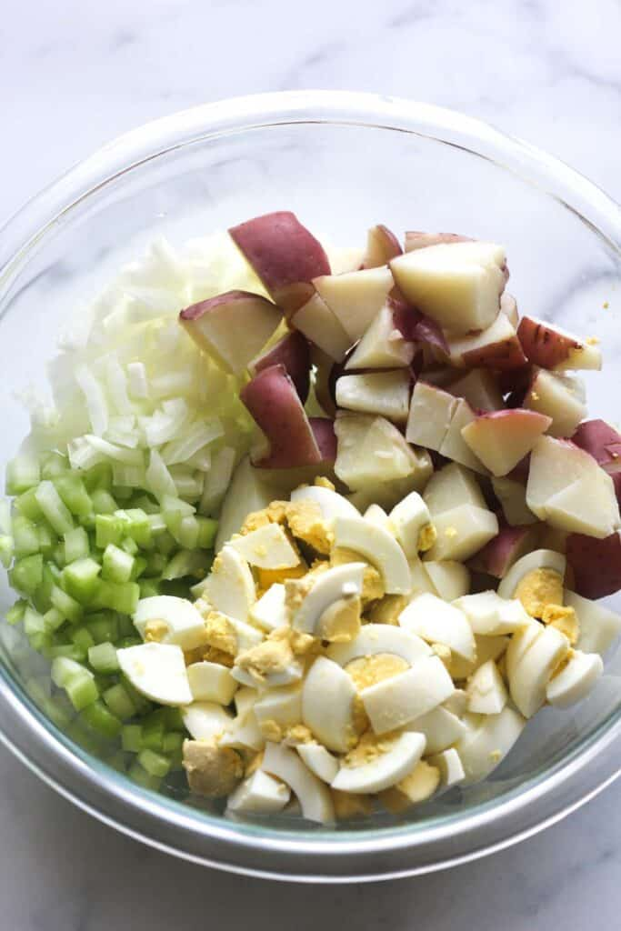 chopped eggs, red potatoes and onions and celery in a glass bowl