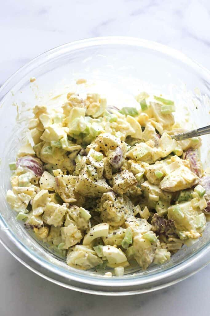 mixed potato salad in a glass bowl with black pepper on top