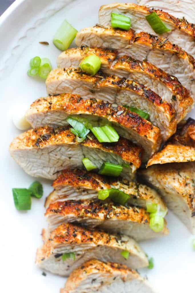ninja foodi turkey tenderloin on the white plate with chopped green onions on top