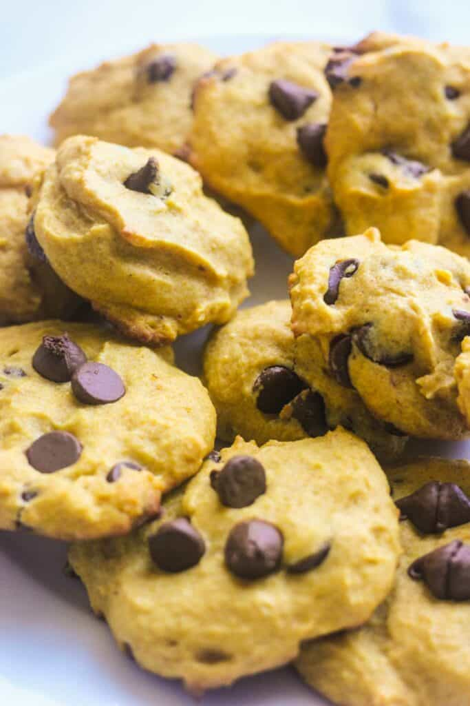 many pumpkin ricotta cookies with chocolate chips on top of each other