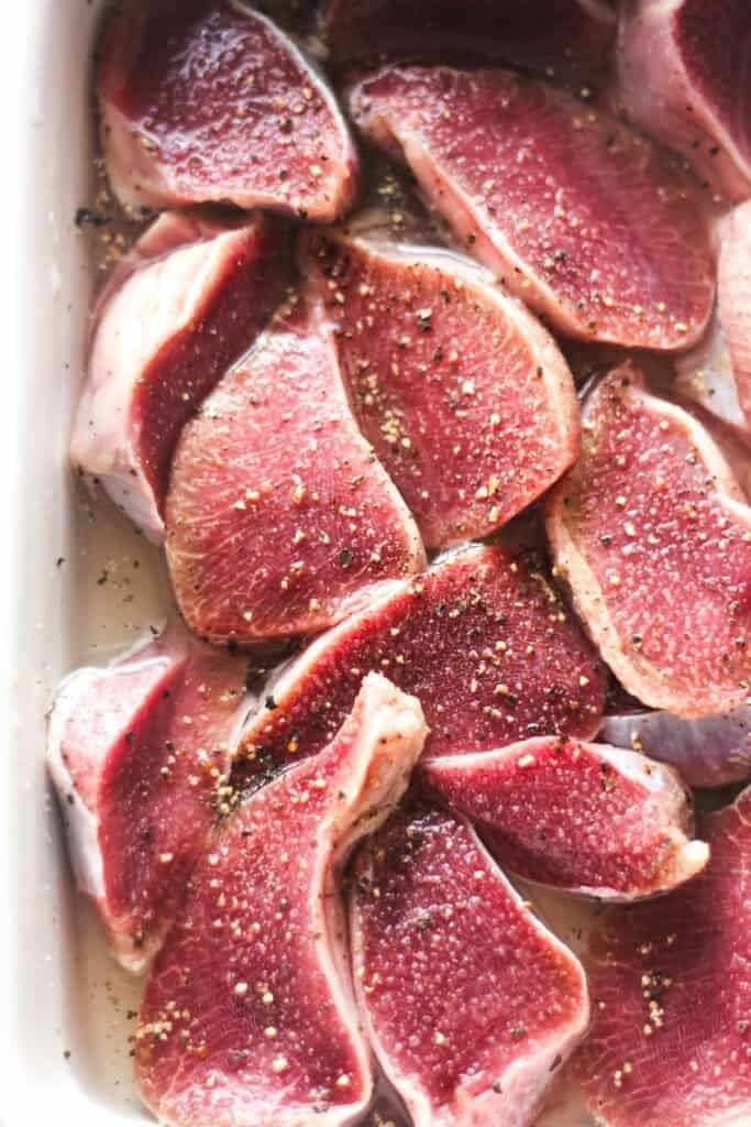 raw sliced giblets with salt and black pepper in the white baking dish