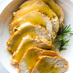 sliced turkey breast with yellow gravy on top